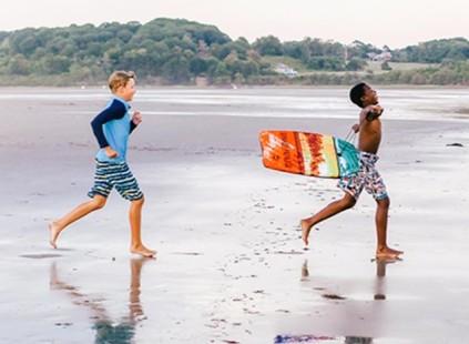 Photo of 2 kids running on the beach.