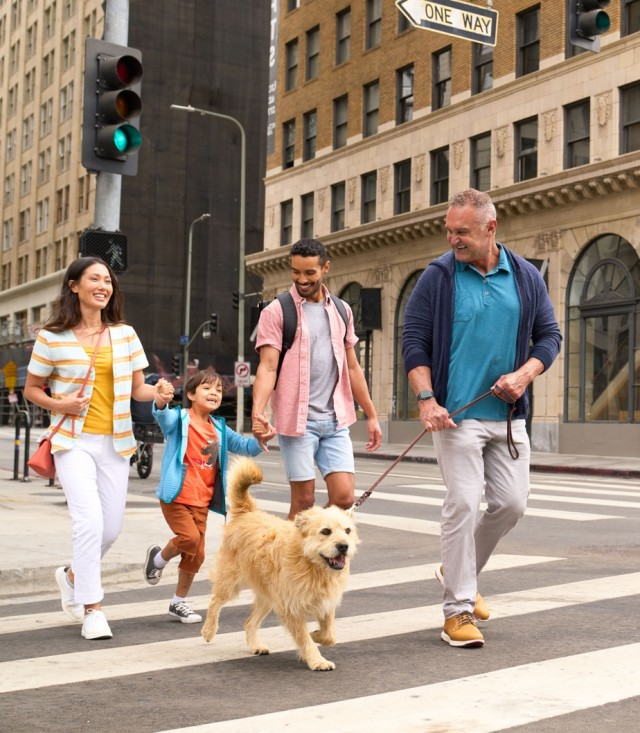 A family walking their dog in the city on the sidewalk.