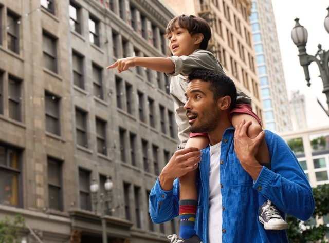 A man with a child on his shoulders walking in the city.