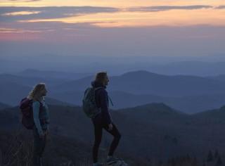 Two women hiking at sunset