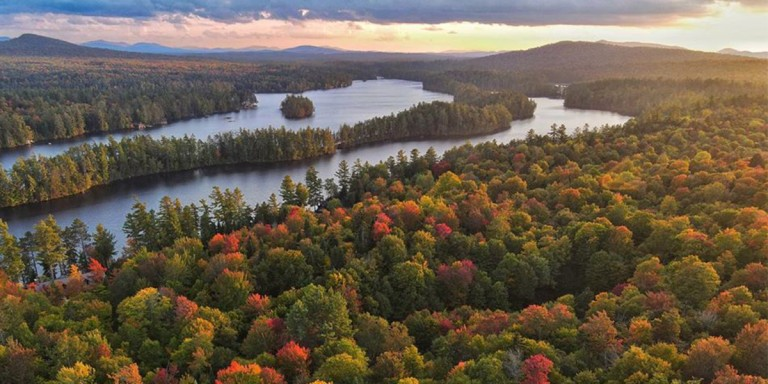 Beautiful vista of trees, water and mountains in the distance, fall colors ablaze.