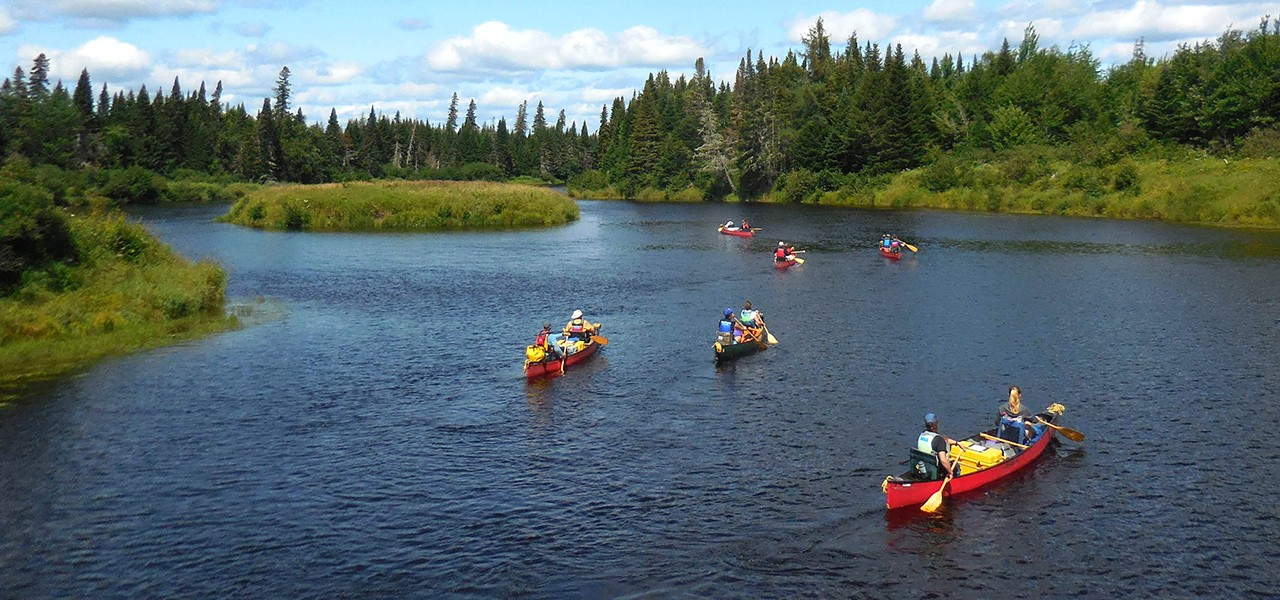 A group of 6 canoes loaded with camping gear and 12 people paddling on calm water on a beautiful day.