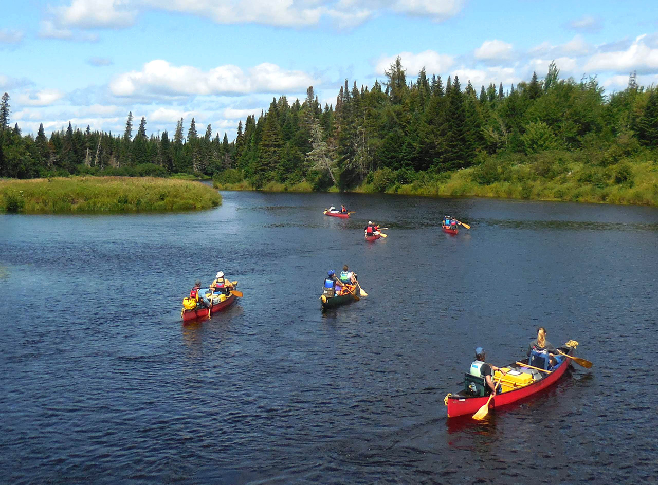 6 canoes packed with camping gear and 12 people paddling on a calm river.