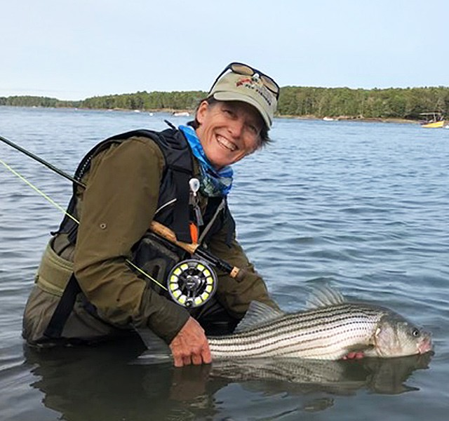 Susan Daignault, with fishing rod under her arm, smiles while standing in thigh-deep water holding a fish.