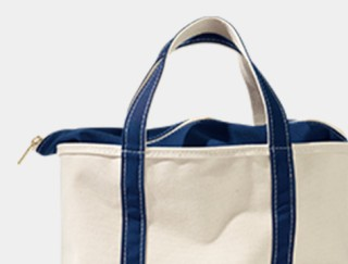 Close-up of a canvas tote bag with zippered top.