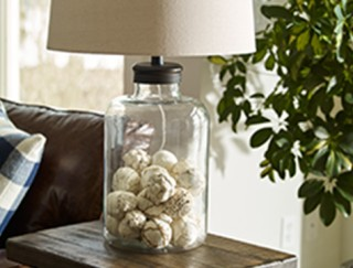 Fillable clear glass lamp on side table.