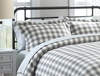 Close-up of bed made up with checked flannel bedding.