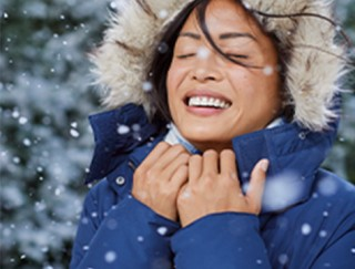 Close-up of woman outside enjoying a light snow.