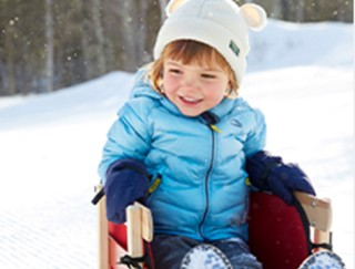 Smiling toddler getting a ride in a sled outside in the snow.