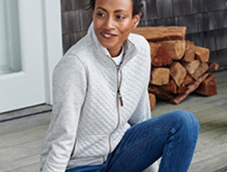 Smiling woman sitting on a porch wearing a quilted sweatshirt.