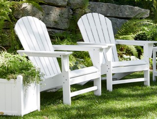 2 adirondack chairs in a back yard.