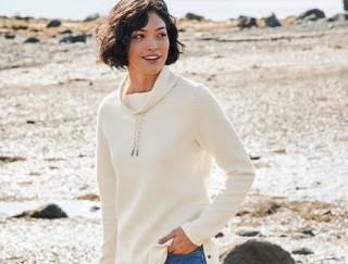 Smiling woman standing on a beach.