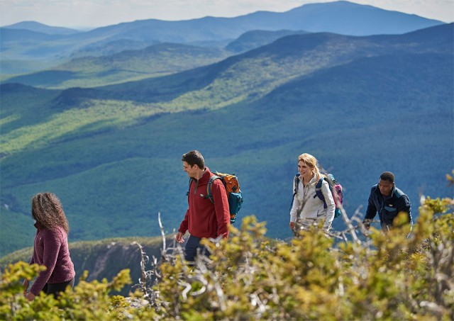 4 friends hiking through a beautiful mountain scene.