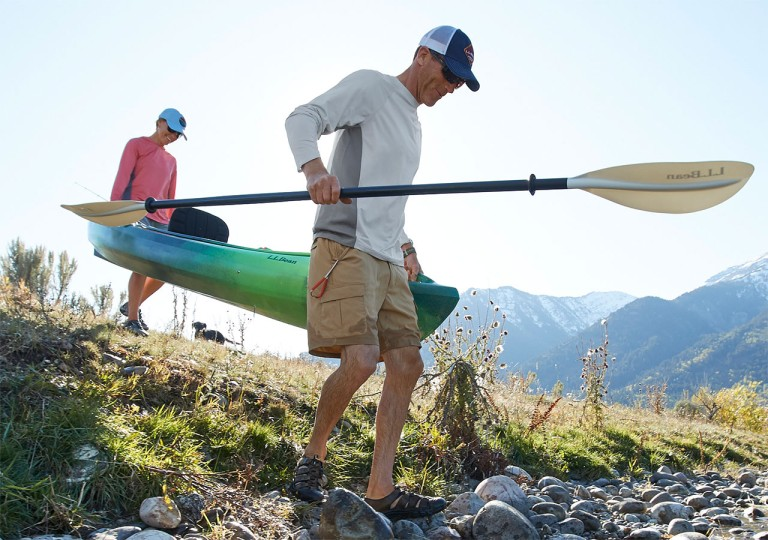2 men carrying a kayak to the water.