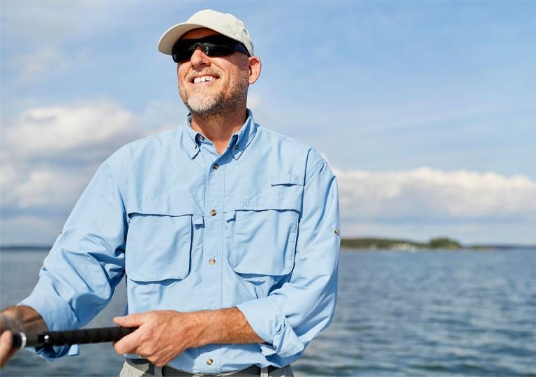Man standing in a boat fishing wearing a SunSmart shirt.