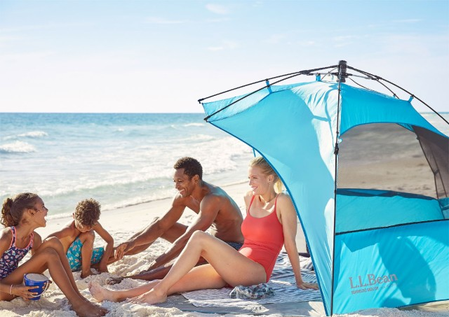 A family of 4 relaxing in and around a sun shelter on the beach.