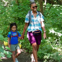 A mom and girl holding hands on a hike.