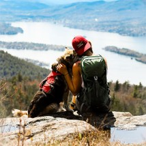A woman with her arm around a dog looking at a magnificent mountain view.