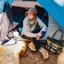 A woman sitting in the doorway of a tent.