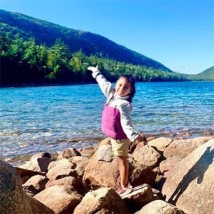A little girl with arms spread wide by a beautiful lake.