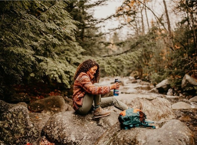 A woman hiker taking a break by a river, sitting on a rock.
