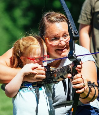 A mom helping her daughter with a bow and arrow