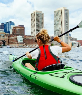A woman kayaking with a city view in the background