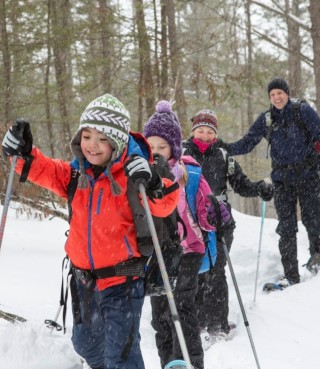 A group of children snowshoeing