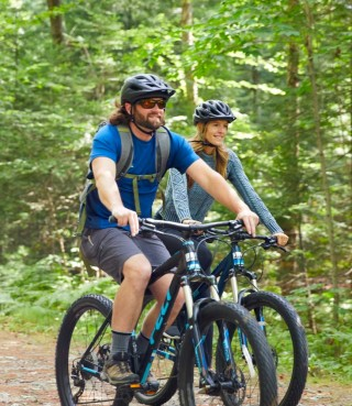 Two people moutain biking in the woods