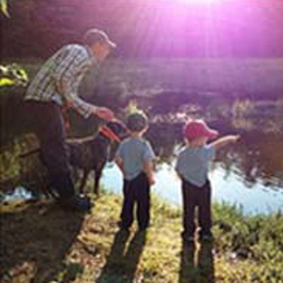 Dad and two boys at the edge of a pond pointing.