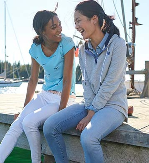 Two female friends sitting on dock.