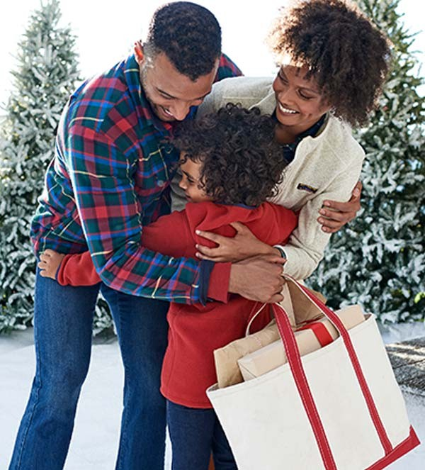 Family with gifts hugging.