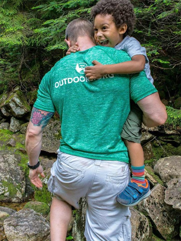 Man carrying a child on a hiking trail.