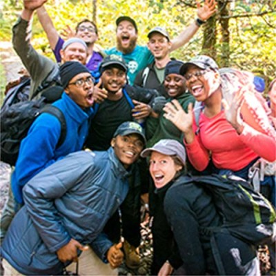 A group of hikers huddle for a photo.