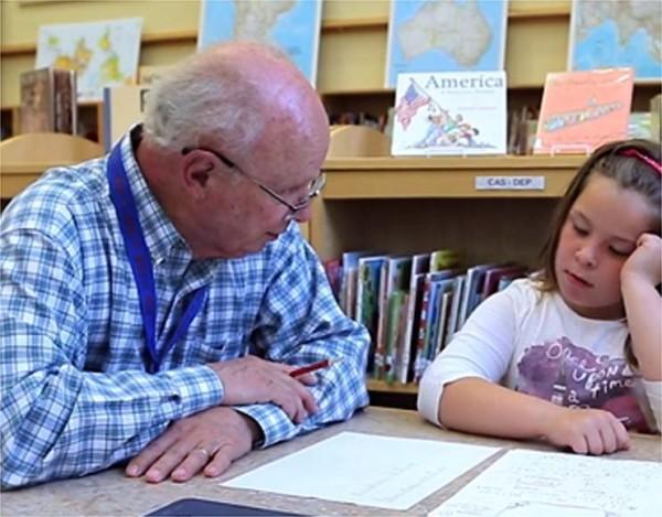 Community volunteer helping an elementary school student.
