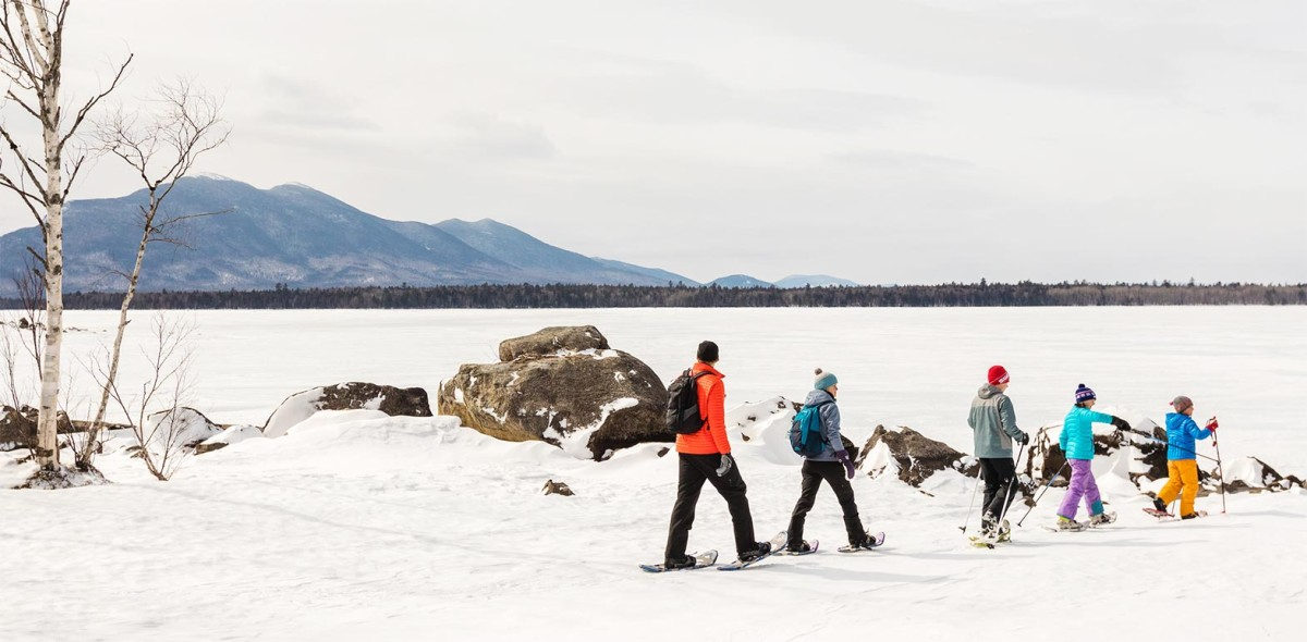 A family snowshoeing alongside Flagstaff Lake.