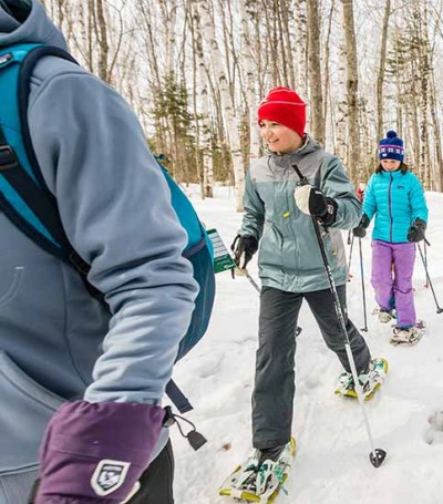 A group of people snowshoeing on a trail.