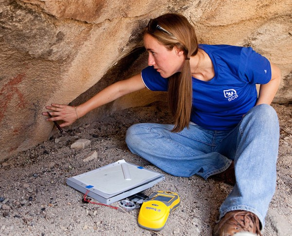 Young girl checking bottom of rock foundation.