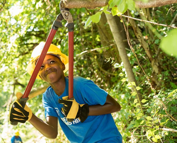 Teen boy using shears to trim trees.