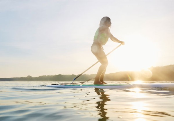 A women paddleboards during an Outdoor Discovery Schools event,