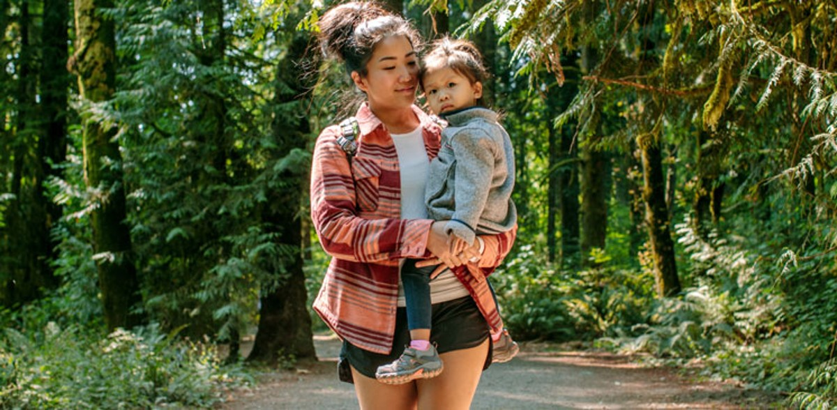 A woman carrying a child while hiking a trail in the woods.