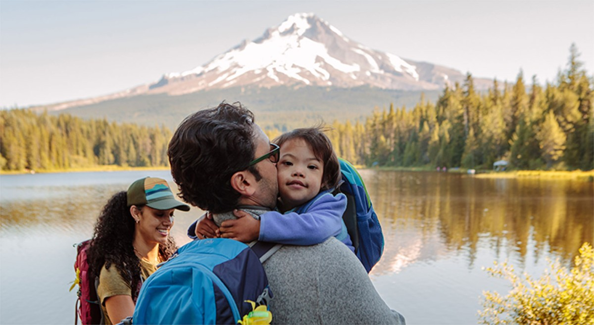 Man, Woman and child hiking with a scenic view of a lake, mountain and forest.