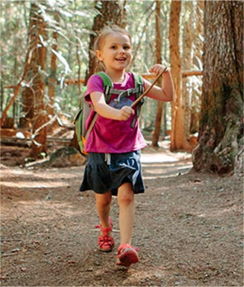 A child hiking a path in the woods.