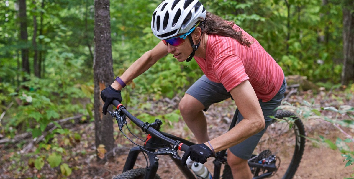 A closeup of L.L.Bean Partner Athlete Lea Davison mountain biking in the woods.