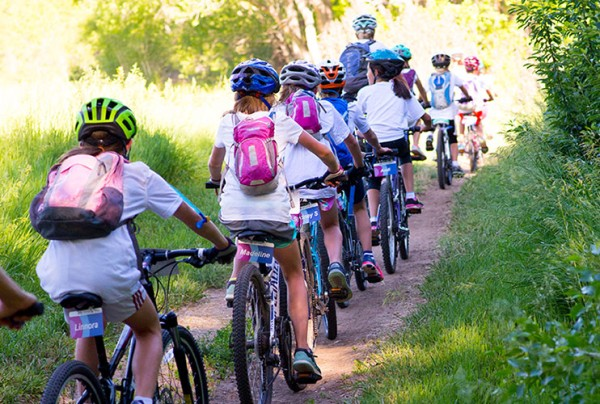 Girls from the LIttle Bellas mentoring program biking together through the woods.