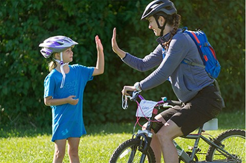 Woman sitting on a bicycle giving the child standing beside her a high-five.