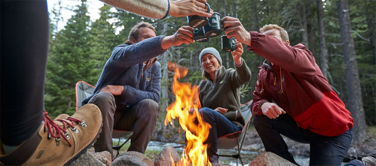 Group toasting with mugs around a campfire.