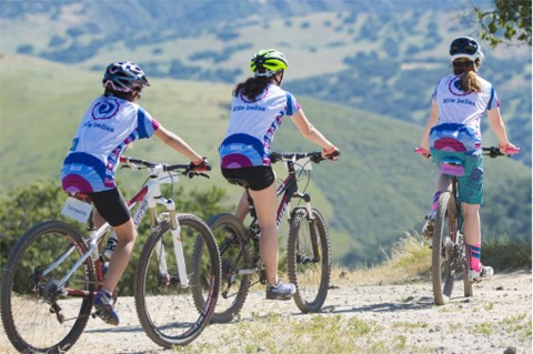Girls ride bikes through the mountains.