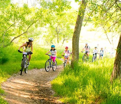 Little Bellas participants ride bikes through the woods.