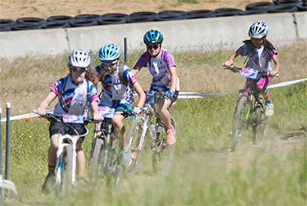 Little Bellas participants riding bikes through a field.